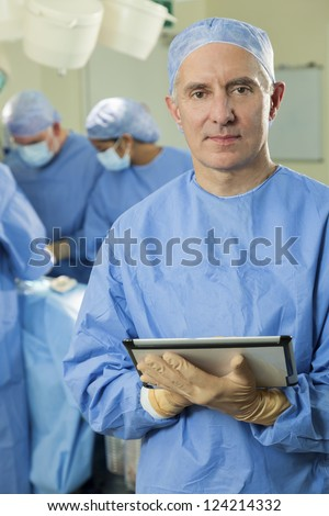 Senior male doctor surgeon using tablet computer with his interracial surgical team working on a patient in hospital operating theater in the background - stock photo