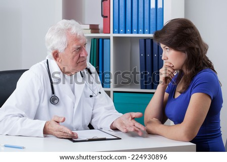 Senior male doctor talking with worried patient - stock photo