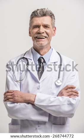 Senior male doctor with crossed hands on grey background. - stock photo