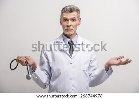 Senior male doctor with stethoscope on grey background. - stock photo