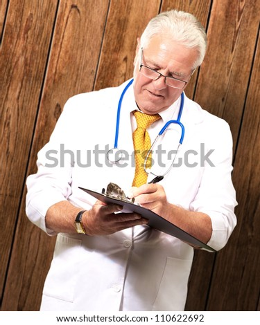 Senior Male Doctor Writing On Clipboard On Wood - stock photo