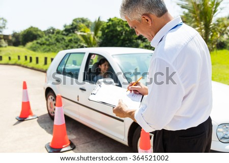 senior male driving instructor testing student driver in testing ground