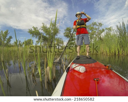 senior male enjoying workout on stand up paddleboard (SUP), calm lake in Colorado during springtime - stock photo