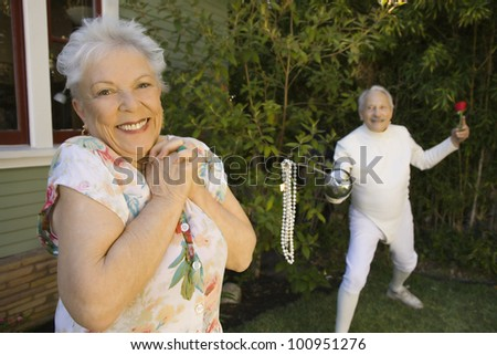 Senior male fencer with pearls at end of epee for senior woman - stock photo