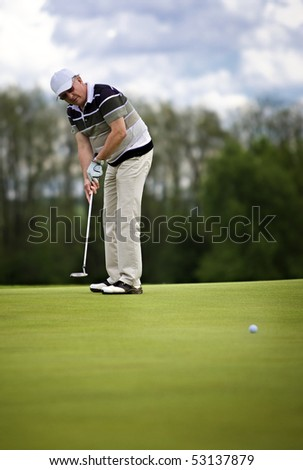 Senior male golf player putting a golf ball on the green.