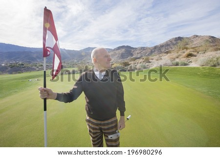 Senior male golfer looking away while holding flag and putter at golf course - stock photo