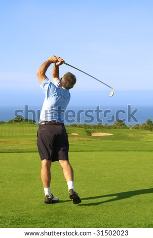 Senior male golfer playing golf from the tee box next to the ocean on a beautiful summer day - stock photo