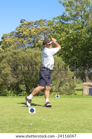 Senior male golfer playing golf from the tee box on a beautiful summer day