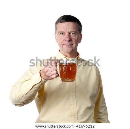 Senior male holding a pint of brown ale in english style mug and raising the drink in a greeting - stock photo