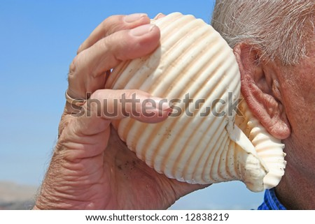 Senior male holding a shell to his ear.