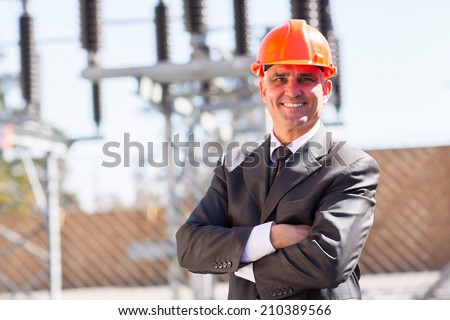 senior male industrial engineer in electricity substation with arms crossed - stock photo