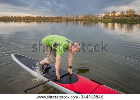 senior male is starting  paddling workout on his stand up paddleboard on a lake in Colorado - stock photo
