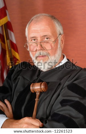 Senior male judge in a robe with a gavel in front of the American flag