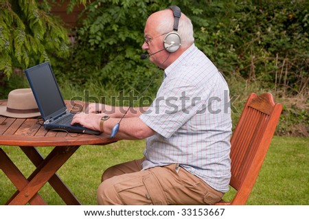 senior male outside using laptop to make voip call - stock photo