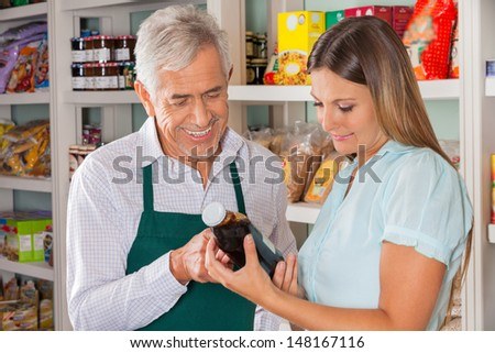 Senior male owner assisting female customer in choosing product at store - stock photo