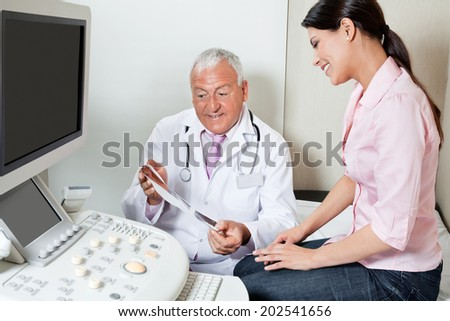 Senior male radiologist showing ultrasound print to female patient at clinic - stock photo
