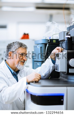 Senior male researcher carrying out scientific research in a lab (shallow DOF; color toned image) - stock photo