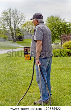 Senior male spraying his lawn with weed killer - stock photo
