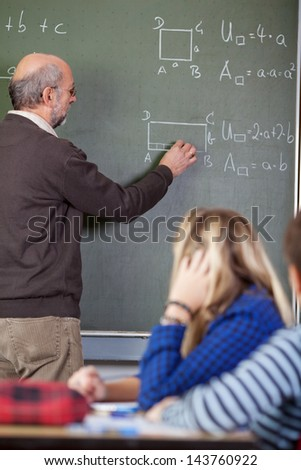 Senior male teacher solving sums on blackboard with students in foreground at classroom - stock photo