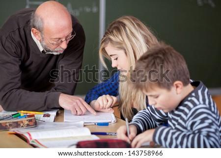 Senior male teacher teaching student at desk in classroom - stock photo