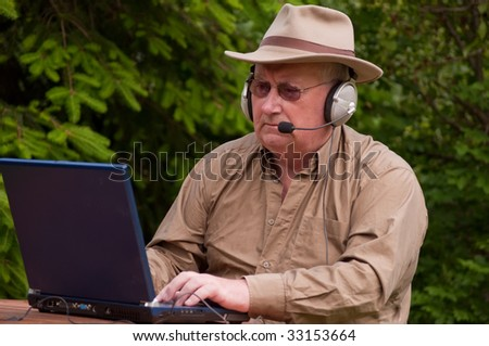 senior male using laptop with headphones - stock photo