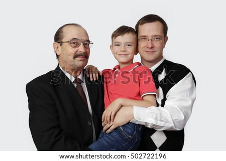 Senior man, adult man and boy group portrait on gray background - Three men generations of one family together