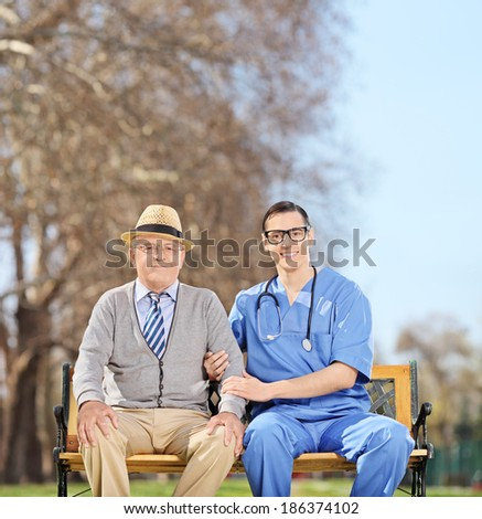 Senior man and a male doctor posing in park shot with tilt and shift lens - stock photo