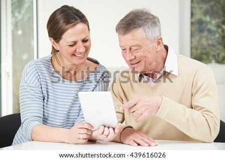 Senior Man And Adult Daughter Looking At Digital Tablet Together