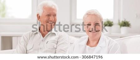 Senior man and adult nurse in white - stock photo