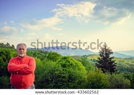 Senior man and beautiful mountain landscape. Looking at the camera. Serious senior man with gray hair and beard. Horizontal image. - stock photo