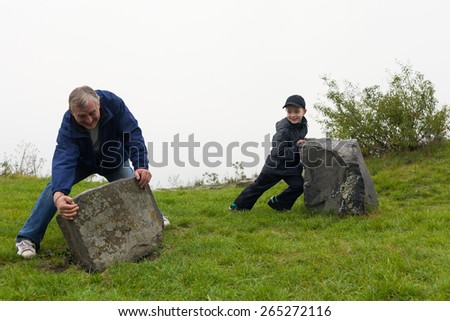 Senior man and child boy trying to move big boulders outdoors. - stock photo