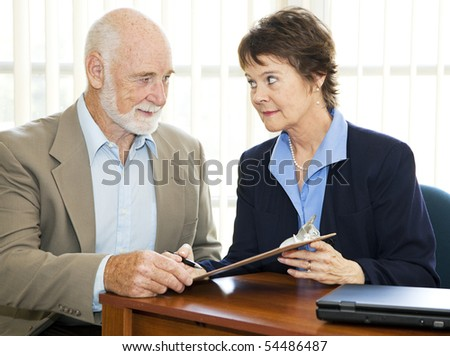 Senior man and his agent or broker having a serious discussion before he signs paperwork. - stock photo