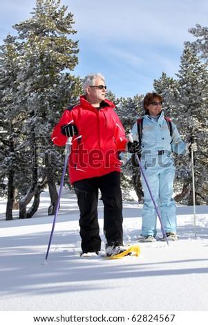 Senior man and senior woman snowshoeing on snow - stock photo