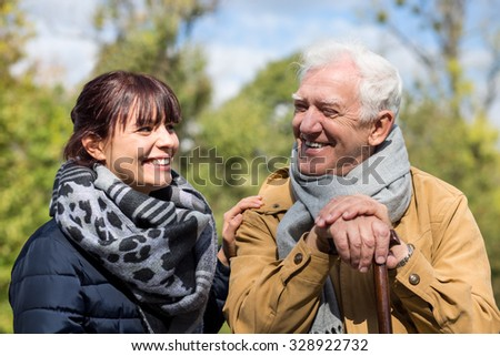 Senior man and social worker spending time outdoors - stock photo
