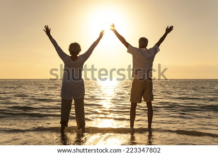 Senior man and woman couple arms raised celebrating together at sunset or sunrise on a beautiful tropical beach - stock photo