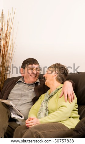 Senior man and woman couple reading newspaper sitting on sofa in lounge, with copyspace above - stock photo