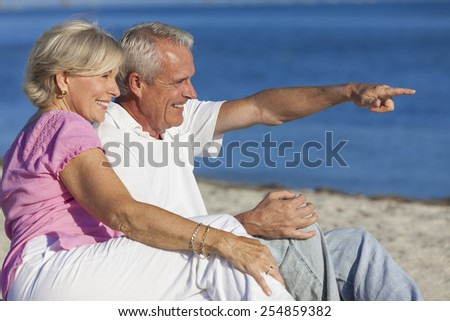Senior man and woman couple sitting on a deserted beach pointing to the sea - stock photo