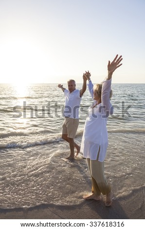 Senior man and woman couple walking together at sunset or sunrise on a beautiful tropical beach - stock photo