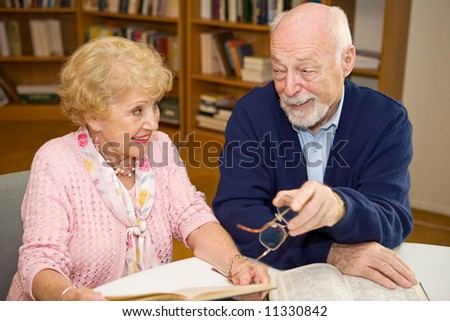 Senior man and woman meeting at the library and discussing books. - stock photo