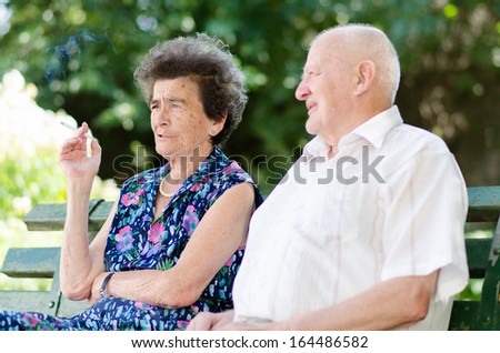 Senior man and woman smoking outdoor