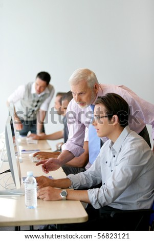 Senior man and young man in front of a desktop computer - stock photo