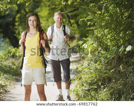 senior man and young woman walking with backpack in wood, looking at camera and smiling. Horizontal shape, front view, copy space - stock photo