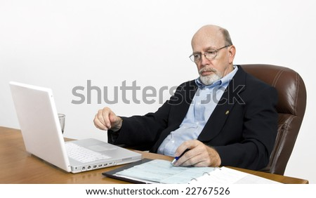 Senior man at his computer viewing his financial future with doubt and worry. - stock photo