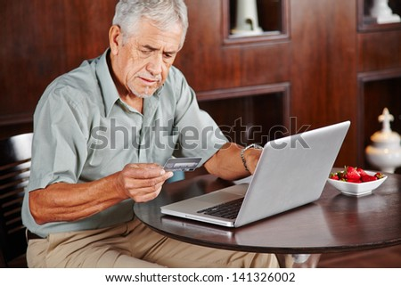 Senior man at laptop paying with credit card for online shopping - stock photo