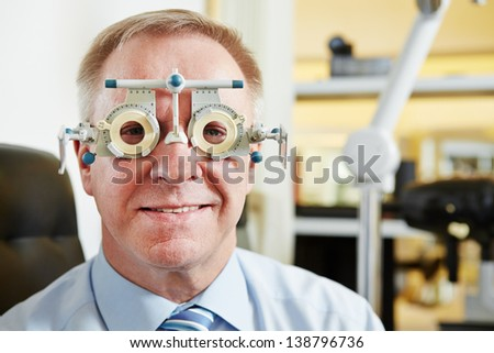 Senior man at optician with trial frame for lens determination - stock photo