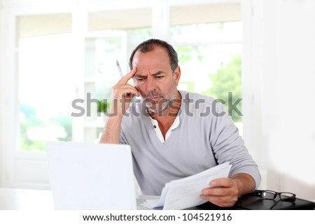 Senior man being puzzled with tax documents - stock photo