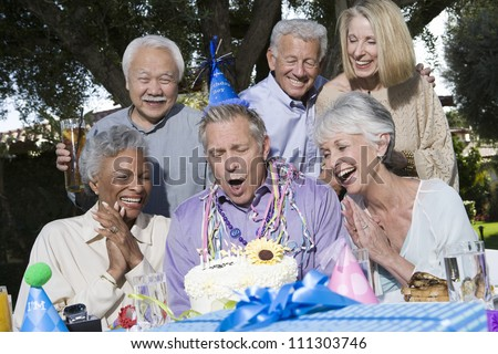 Senior man blowing candles with family and friends - stock photo