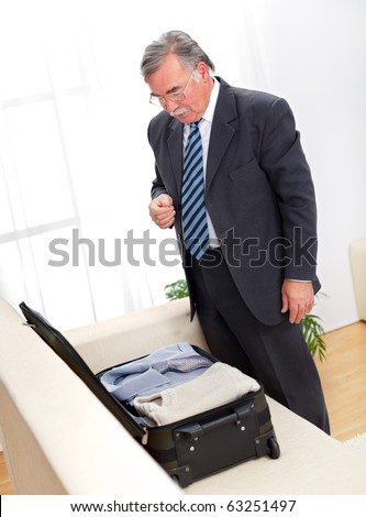 Senior man checking the suitcase before or after journey