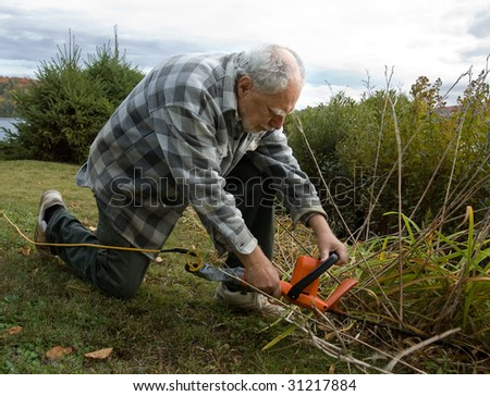 senior man cleaning the garden with an edger - stock photo