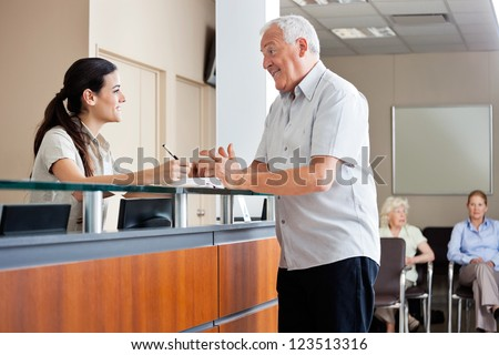 Senior man communicating with female receptionist while women sitting in background